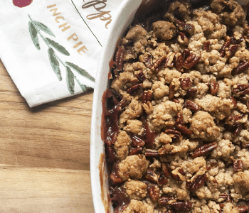 Apple cherry crumble with crispy topping on cutting board.