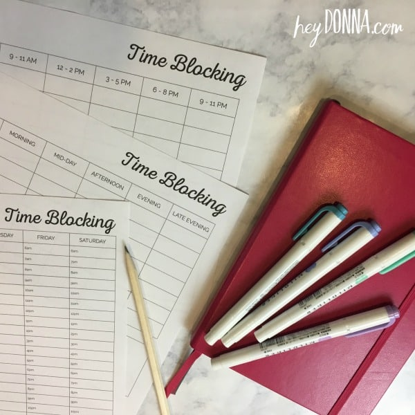 Time Blocking Calendar printables on table with pink notebook and pens.