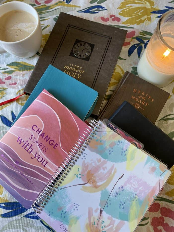 Notebook, devotional and planners on table with coffee and candle.